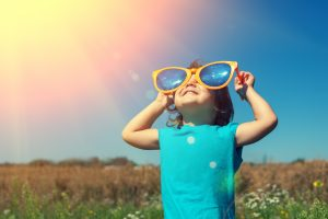 little girl with sunglasses on looking to the sun
